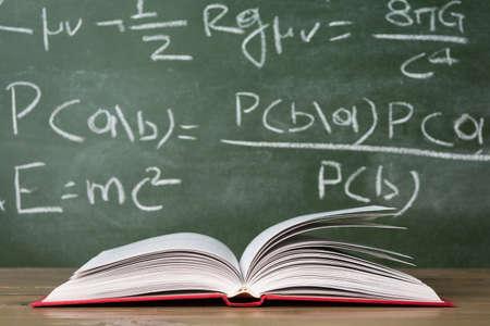 Open book against green chalkboard, close up Standard-Bild