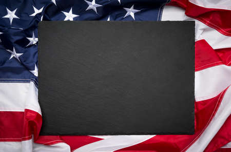Blank slate board over American flag as a concept for US national celebrations