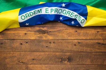 Brazilian flag lying on old wooden background Standard-Bild