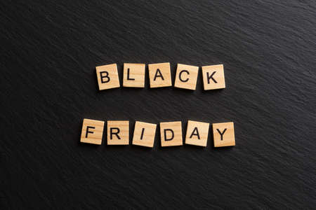 Black Friday sale inscription on wooden tiles on a black textured background