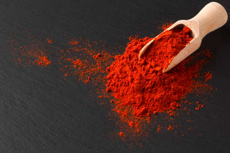 Wooden scoop with ground paprika on black textured background, close up