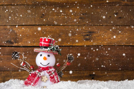 Happy snowman against wooden background with copy-space, as a concept for Merry Christmas and happy new year greeting card