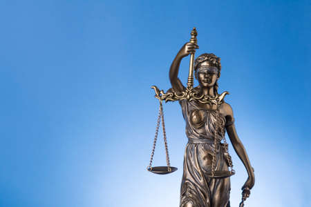 The statue of justice Themis or justitia on blue background