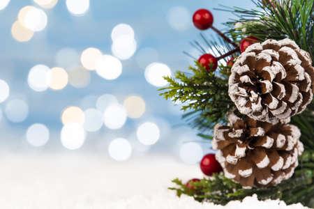 Christmas tree branch on snow with bokeh glittering lights Standard-Bild