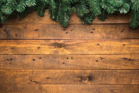 Fir garland hanging on a blank rustic wooden background, as a Christmas season concept Standard-Bild