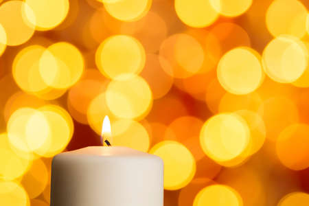 White burning candle against golden bokeh lights Standard-Bild