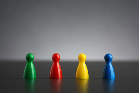 Group of four figurines in different colors in a row Standard-Bild