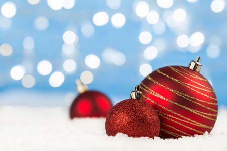 Christmas red balls on snow with gold and bokeh lights Standard-Bild