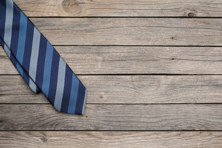 Blue striped tie over old wooden background as a concept for happy father's day clebration