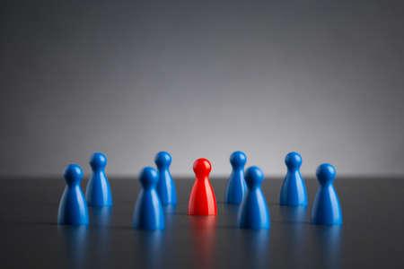 Selective focus on single red figure among blue group Standard-Bild