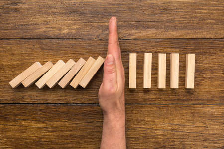 Stopping the domino effect concept Standard-Bild