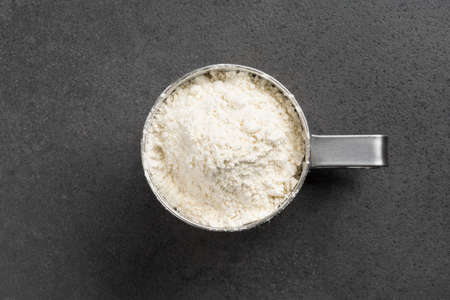 Stainless steel sifter full of flour on grey background