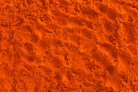 Full frame of red ground paprika background texture
