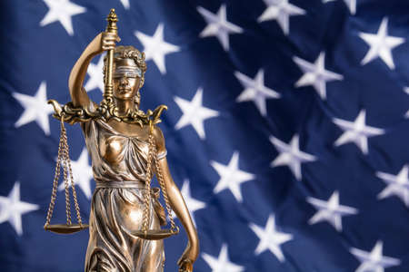 The statue of justice Themis or Justitia, the blindfolded goddess of justice against the flag of the United States of America, as a legal concept Standard-Bild