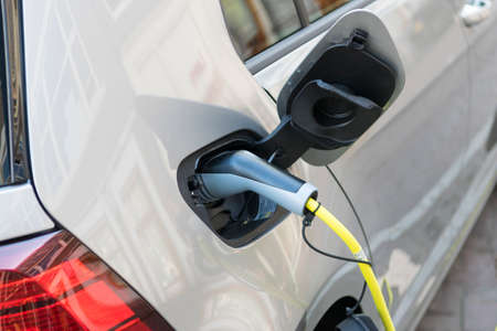 Close up of the power supply plugged into an electric car. Eco car concept