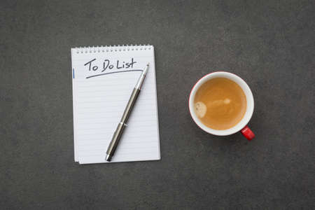 Notepad with the to do list and red coffee cup on grey desk. High angle view