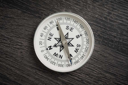 Old compass on dark wooden surface Stock Photo