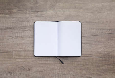 High angle view of blank opened note pad on wooden background.