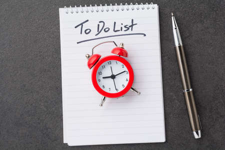 Alarm clock over spiral note pad with the to do list as a time management concept Standard-Bild