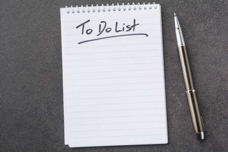 High angle view of a notepad with the to do list and a pen on grey desk Standard-Bild