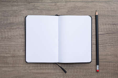 High angle view of blank opened note pad and black pencil on wooden background.