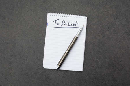 High angle view of a notepad with the to do list and a pen on grey desk Stock Photo