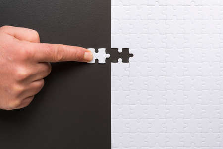 Male hand holds the last piece of the puzzle