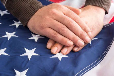 Male hands touch the flag of the United States of America