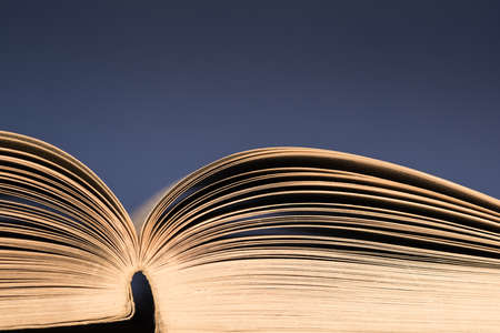Open book on blue background, close up