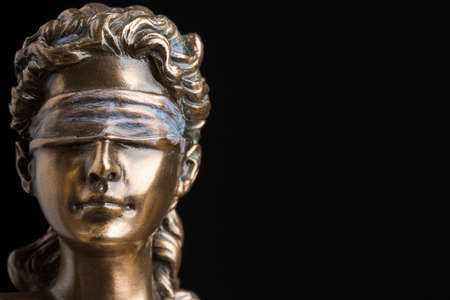 Portrait of the blindfolded goddess of justice Themis isolated on black background with copy space, as a legal concept