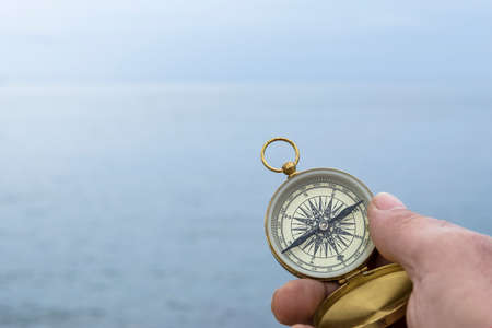 Man holds a compass against the horizon of the sea on a foggy day. Selective focus