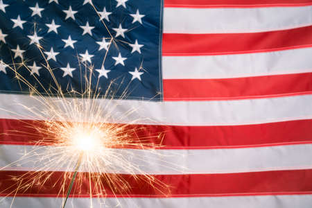 Glowing sparkler against US flag with copy space