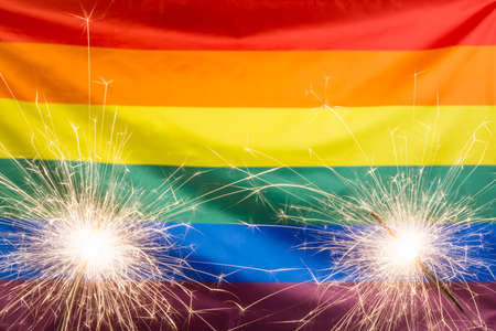 Glowing sparklers against waving rainbow flag with copy space Stock Photo