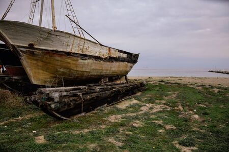 Old wooden boat left rotting on the shore