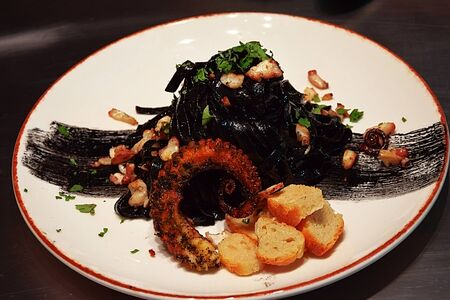 Tagliatelle on Cuttlefish ink, with a unique black Caesars and caramelized octopus Banco de Imagens