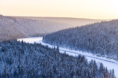 River under the ice, and all around fabulous snowy coniferous forest during sunset