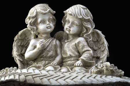 Two beautiful angels sitting on the black background photo