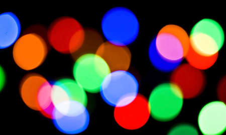 Blurred colorful festive lights at night useful as background over black  photo
