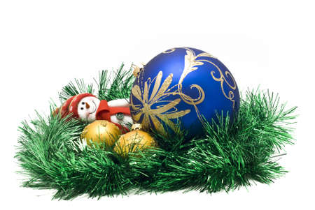 Christmas toy with three colorful New Year decoration Balls and green tinsel over white photo