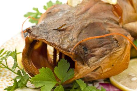 sheatfish: Detalle de hinchados de cabeza de sheatfish con lim�n y perejil en el plato sobre blanco  Foto de archivo