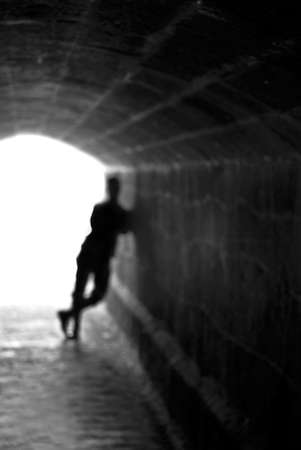 elysium: Blurred human silhouette against the light of tunnel exit background (shallow DOF)