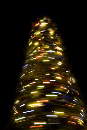 rotative: Blurred rotating New Year tree at night over black