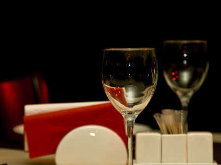 Restaurant - wineglasses and table appointments in the dark (focus on wineglass, shallow DOF) photo