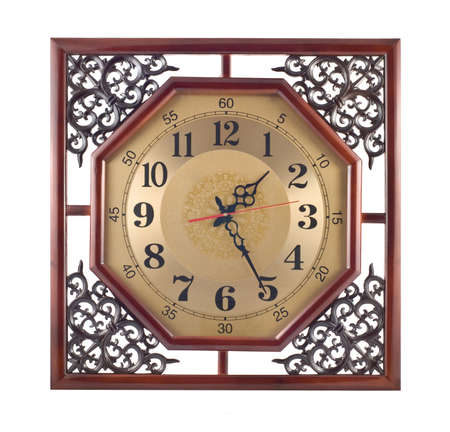 Antique wall clock with carved wooden frame isolated over white photo