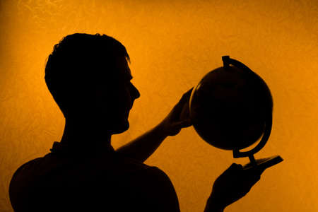 Hold the World - silhouette of man holding globe in the darkness photo