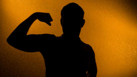 strong arm: Strength and health - silhouette of man in the darkness