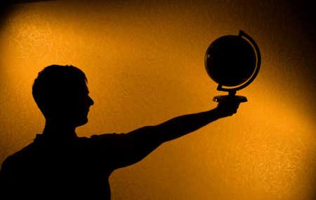 el mundo en tus manos: Mundo en sus manos - silueta del hombre en la oscuridad Foto de archivo