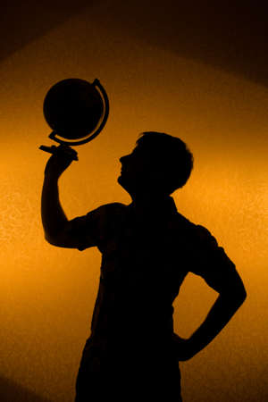 Back light - silhouette of man holding globe in the dark photo