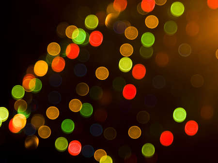 out of focus: Blurred festive colorful lights over black useful as background