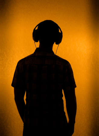 listening back: Listen to the Music - silhouette of man with headset (back light) Stock Photo